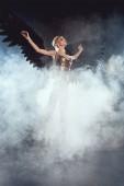 Fotografie schöne sexy Frau mit schwarzer Engelsflügel springen auf rauchigen Hintergrund