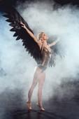 Krásná sexy žena s černým andělská křídla a natažených rukou pózuje na tmavé kouřové pozadí