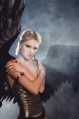 krásná mladá sexy žena s černým andělská křídla a zlaté doplňky pózuje na tmavé kouřové pozadí