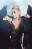 Fotografie schöne sexy Frau in goldenen Accessoires halten schwarze Engelsflügel und posiert auf dunklem Hintergrund