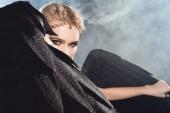 Fotografie Krásná sexy žena v zlaté příslušenství držící černá andělská křídla a Pózování na tmavém pozadí