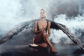 Photo beautiful sexy woman with black angel wings sitting, looking at camera and posing on dark background