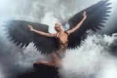 Fotografie Krásná sexy žena s černým andělská křídla a natažených rukou sedí a Pózování na tmavé kouřové pozadí