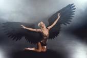 szép szexi nő, a fekete angyal szárnyak és a kinyújtott kezet, ül, és pózol a sötét háttér