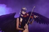 krásná žena v krajkové masky a černá andělská křídla hrají housle na fialové pozadí