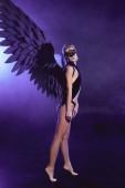 Krásná sexy bosá žena v krajkové masky a černé angel wings pózuje na fialové pozadí