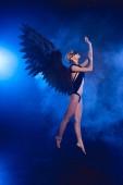 szép szexi nő csipke maszk, és ugrás a sötét kék háttér fekete angyal szárnyak