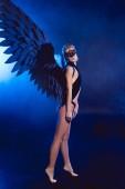 Fotografie schöne sexy Frau mit Spitzen-Maske und schwarzer Engelsflügel stehen auf Zehenspitzen auf dunkelblauem Hintergrund