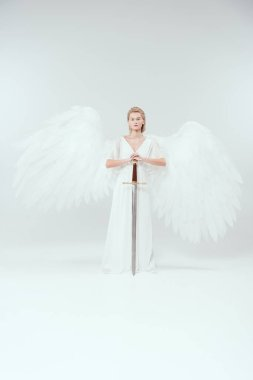 Beautiful woman with angel wings holding sword and posing on white background stock vector