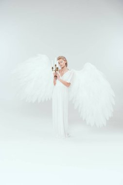 Beautiful tender woman in angel costume with wings holding candelabrum with candles isolated on white stock vector