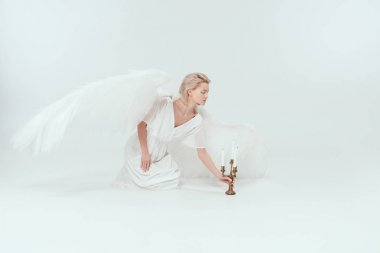 Beautiful woman in angel costume with wings sitting near candelabrum with candles on white background stock vector