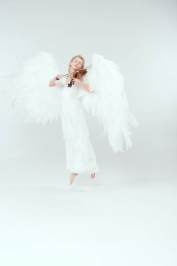 beautiful woman in angel costume with wings jumping and playing violin isolated on white