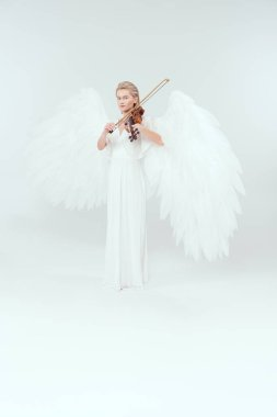 beautiful woman in angel costume with wings looking at camera and playing violin isolated on white