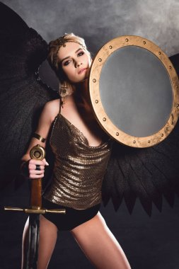 Beautiful sexy woman in warrior costume and angel wings posing with shield and sword on dark background stock vector
