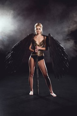 beautiful woman in warrior costume with angel wings holding sword, looking at camera and posing on black smoky background
