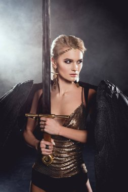beautiful woman in warrior costume with black angel wings holding sword and posing on dark smoky background
