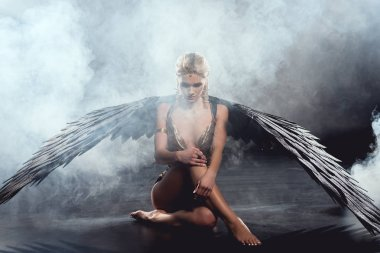 beautiful sexy woman with black angel wings sitting and posing on dark background
