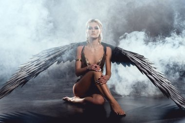 beautiful sexy woman with black angel wings sitting, looking at camera and posing on dark background