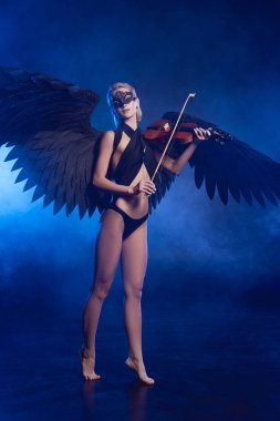 Beautiful sexy barefoot woman with lace mask and black angel wings playing violin on dark blue background stock vector