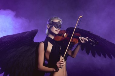 beautiful woman in lace mask and black angel wings playing fiddle on violet background