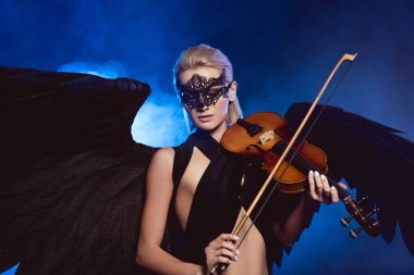 beautiful sexy woman with lace mask and black angel wings playing violin on dark blue smoky background