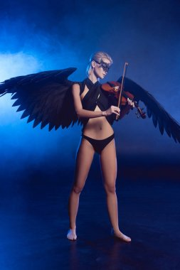 beautiful sexy woman with lace mask and black angel wings playing violin on dark blue background
