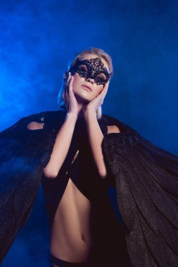 beautiful mysterious woman with lace mask and black angel wings posing on dark blue background