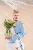 Fotografie krásná dívka stojící s motýly na eco oblečení a drží skleněnou vázu s květinami na béžové pozadí, ekologické ukládání konceptu