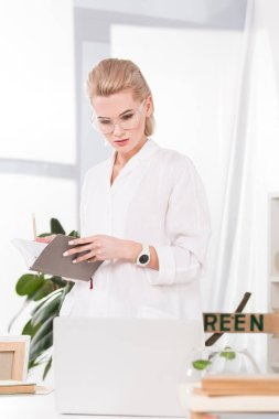 Attractive businesswoman in glasses holding notebook in office stock vector