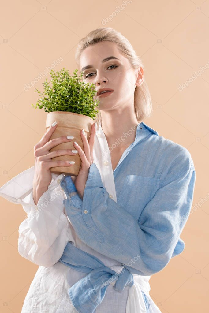 Beautiful woman holding pot with plant and standing in eco clothing isolated on beige, environmental saving concept