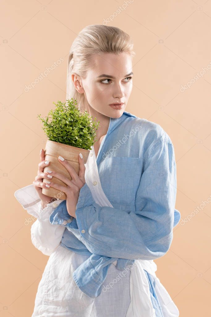 Woman holding pot with plant and standing in eco clothing isolated on beige, environmental saving concept