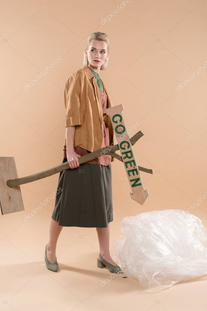 Blonde girl wearing eco clothing standing near polyethylene and holding wooden sign with go green lettering on beige background, environmental saving concept
