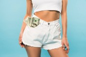 abgeschnittene Ansicht von sexy Mädchen in weißen Shorts mit Dollarnoten in der Tasche auf blauem Hintergrund