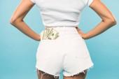 Fotografie Ansicht von sexy Mädchen in kurzen Hosen mit Dollar-Banknoten in Tasche auf blauem Hintergrund abgeschnitten