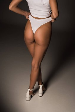 Partial view of sexy young woman in white underwear on dark background