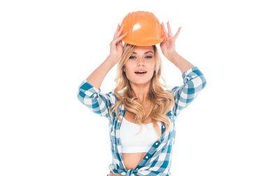 Attractive blonde handy woman in blue shirt putting on hardhat isolated on white stock vector