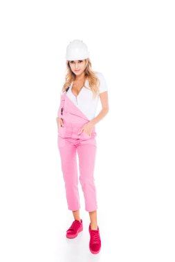 Handy woman in pink overalls and hardhat on white background stock vector