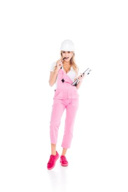 Handy woman in pink overalls, hardhat with paper clipboard pen on white background stock vector