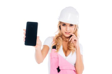 handy woman in pink overalls standing and holding smartphone with blank screen isolated on white