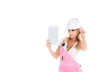 Handy woman in pink overalls standing with digital tablet isolated on white stock vector