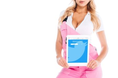 Cropped view of handy woman in pink uniform holding digital tablet with twitter app on screen isolated on white stock vector