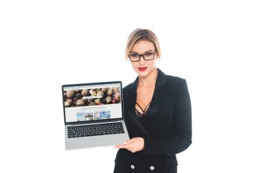 attractive businesswoman in black formal wear holding laptop with depositphotos website on screen isolated on white
