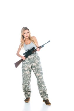 Attractive blonde militarywoman in grey t-shirt and camouflage pants standing with rifle isolated on white stock vector
