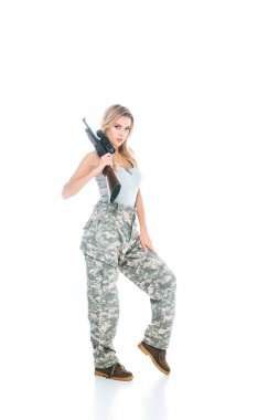 Blonde militarywoman in grey t-shirt and camouflage pants standing with rifle on white background stock vector