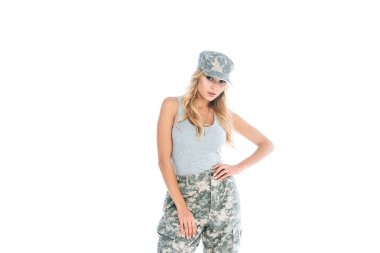 attractive militarywoman in grey t-shirt, camouflage pants and cap isolated on white
