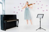 Fényképek floating girl in blue dress playing violin near piano on white background with butterflies