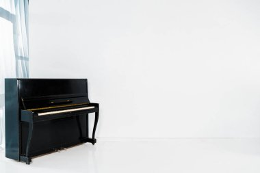 black piano on white background with copy space