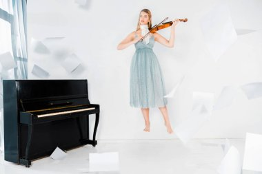floating girl in blue dress playing violin with sheets of paper in air on white background