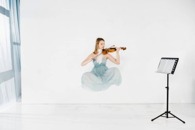 floating girl in blue dress playing violin with music stand on white background
