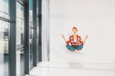 floating girl in jeans and plaid shirt meditating on white background